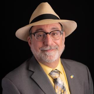 Headshot of Scott Lissner, wearing panama fedora hat, glasses, and a grey suit and